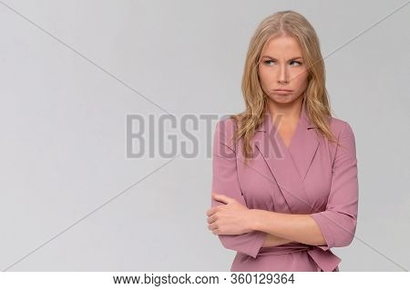 Portrait Of Unhappy Young Woman With Messy Blonde Hair In Dress Standing, Looking Dissatisfed And Ti