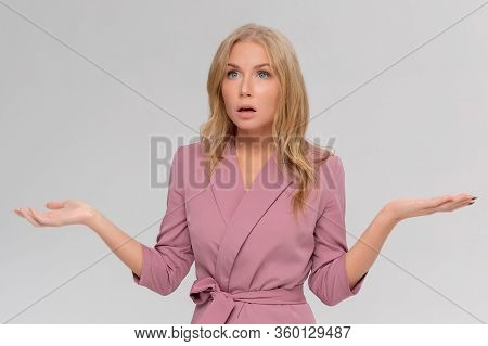 Studio Portrait Of Cute Puzzled Hesitant Young Woman Shrugs Shoulders, Does Not Know What Happened.
