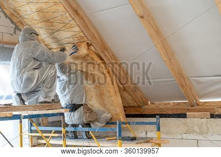 Back View Of Two Professional Worker In Overalls Working Together With Rockwool Insulation, Standing