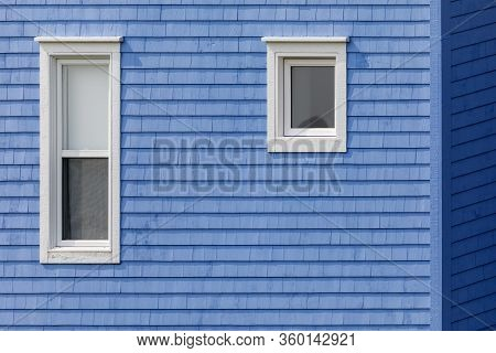 White Windows On Blue Shingled Wall. Typical Colourful Architecture Of Iles De La Madeleine In Canad