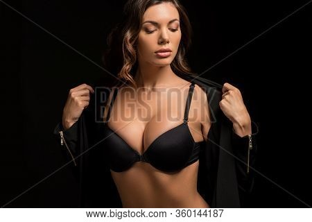 Confident, Seductive Girl In Black Bra Undressing Isolated On Black