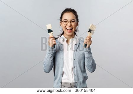 Creativity, Repairs And Overhaul Concept. Excited Happy, Smiling Asian Woman Holding Two Painting Br