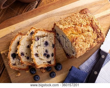 Overhead View Of A Loaf Of Sliced Blueberry Streusel Sweet Bread With Fresh Berries On A Wooden Cutt