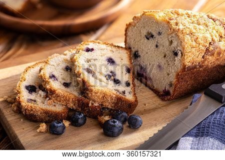 Closeup Of A Loaf Of Sliced Blueberry Streusel Sweet Bread With Fresh Berries On A Wooden Cutting Bo