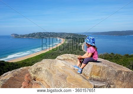 A Little Baby Girl Admiring A View Of The Scenic Landscape Of The Palm Beach In Sydney, Australia