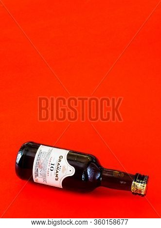 MOSCOW, RUSSIA - APRIL 06, 2020: A bottle of aged Portuguese port wine Grahams on a red background. Copy the text for the text. Illustrative editorial image.