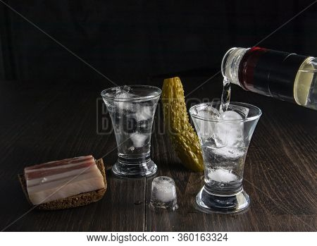 A Bottle Of Vodka, Two Misted Glasses Of Cold Vodka With Ice On A Wooden Board With Bacon And Pickle