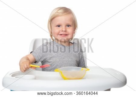 Happy Child Sits In A Highchair And Eats Fruit Puree. A Boy With A Spoon In His Hand On The White Is
