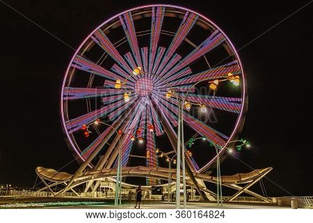 A Colourful Ferris Wheel At Night. Front View. Big Carousel In Baku. Night Fun. Ferris Wheel Against