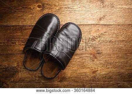 Leather Home Slippers On Wooden Floor. Soft Comfortable Home Slipper. Stay At Home Concepts.