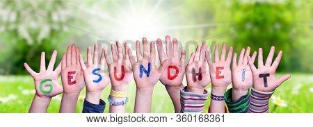 Kids Hands Holding Word Gesundheit Means Health, Grass Meadow