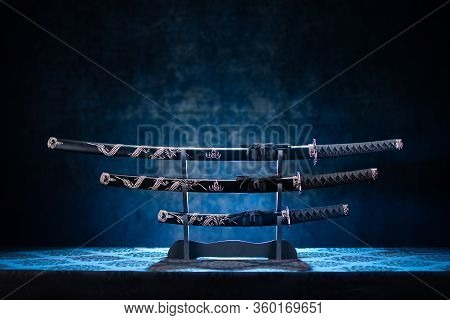 Three Swords On Stand, With Dramatic Blue Light