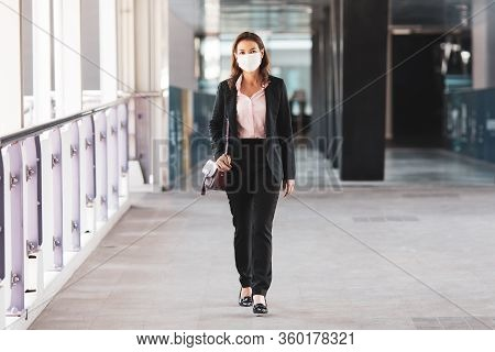 Beautiful Asian Woman In A Black Suit Wearing Medical Hygiene Protective Mask Walking On In City To