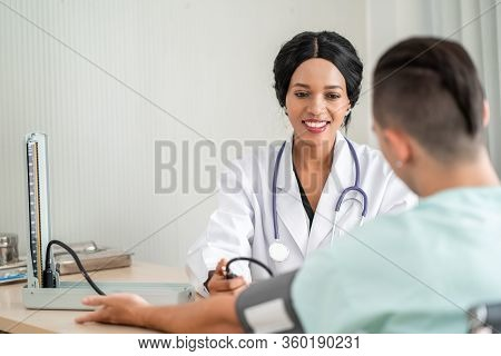 The African American Doctor Is Measuring Blood Pressure For The Patient. And Provide Consultation Re