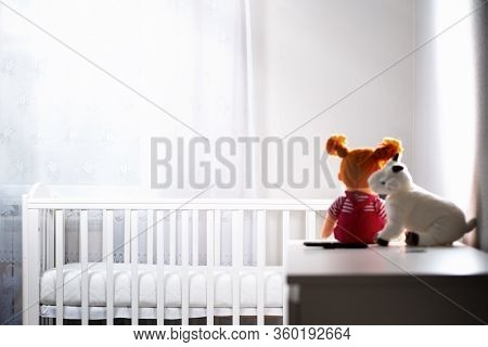 Childrens White Room With An Empty Cradle And Toys On The Dresser. Copy Space. Horizontal. The Conce
