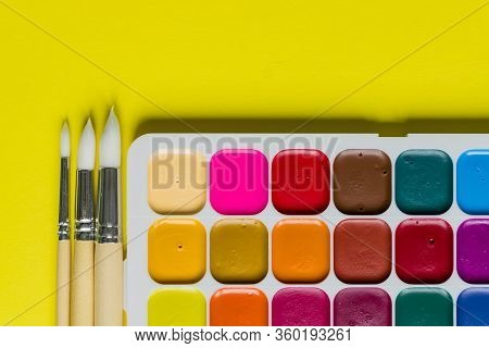 Creative Layout With Aquarelle Palette, Paint Brushes On Yellow Background. Top View. Artists Concep