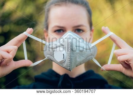Young Girl Putting On Anti-virus Anti-smog Mask On Her Face. Wearing Hygiene Masks Reduces The Risk