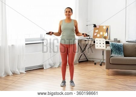 fitness, sport, exercising and healthy lifestyle concept - happy smiling young african american woman skipping with jump rope at home