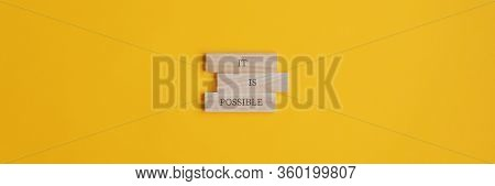 It Is Possible Sign On Stacked Wooden Pegs Placed Over Yellow Background. Wide View Image With Copy