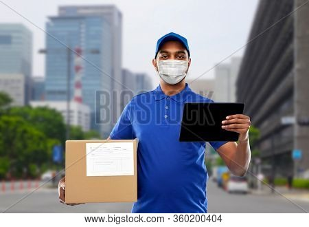 health, safety and pandemic concept - happy indian delivery man wearing face protective medical mask for protection from virus disease with tablet pc and parcel box over city street background