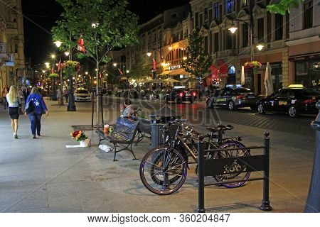Lodz / Poland. 18 July 2019: Night City Street With Bicycles. City Bike Rental At Night. Urban Trans