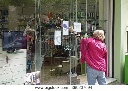 Athens, Greece - March 28, 2020: Customer Paying Pharmacist For Medicine Through Small Porthole Wind