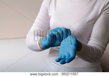 Woman Puts On Protective Blue Gloves. Medical Healthcare. Doctor Hands In Gloves In Hospital. Profes