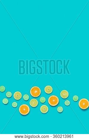 Creative layout made of colorful tropical fruits isolated on blue background. Minimal summer concept. Citrus fruit  pattern.   Flat lay, top view. Orange, Lime, Lemon slices background. Copy space.