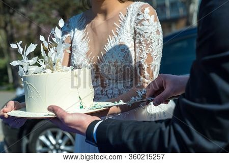 Close Up Of Bride And Groom Cut A Beautiful Wedding Cake. Outdoor. Beautiful White Pastry Wedding Ca