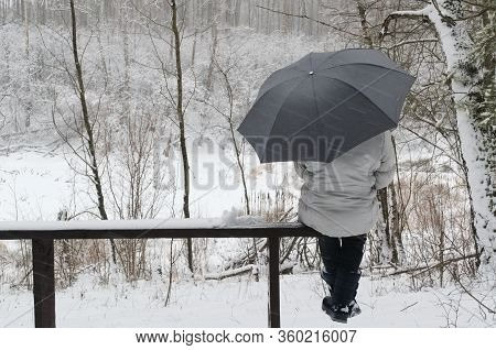 Bad Weather And Single Woman. Woman With Umbrella Sitting On A Snowy Bench On The Background Of A Fo