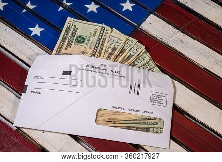 Stack Of 20 Dollar Bills In Irs Envelope To Illustrate Coronavirus Stimulus Payment Or Estimated Tax