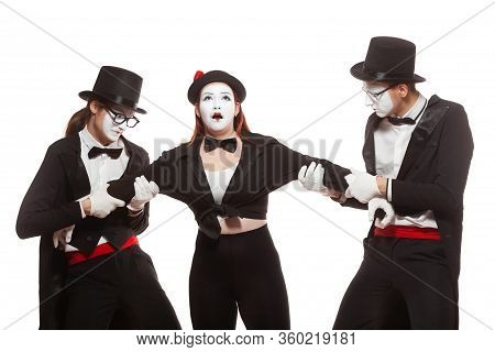 Portrait Of Three Mime Artists Performing, Isolated On White Background. Two Men Pull The Girl To Si