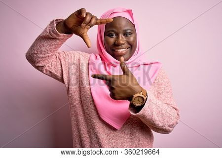 Young african american plus size woman wearing muslim hijab over isolated pink background smiling making frame with hands and fingers with happy face. Creativity and photography concept.