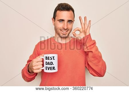 Young handsome man with blue eyes drinking cup of coffe with best dad ever message doing ok sign with fingers, excellent symbol