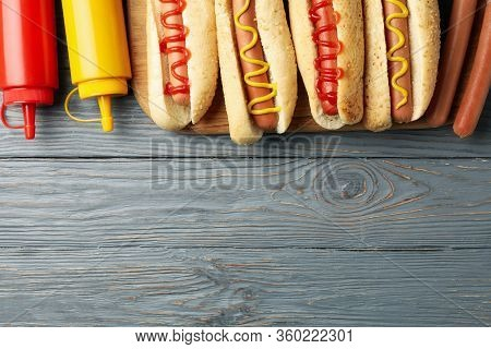 Tasty Hot Dogs And Sauces On Gray Wooden Background