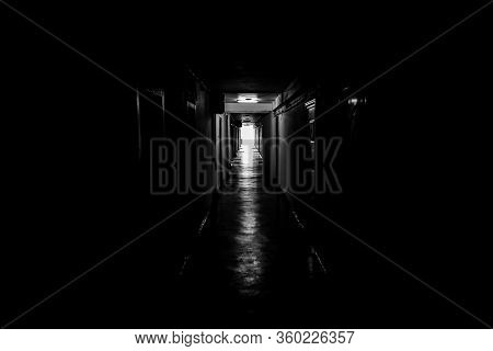 Black And White Image With A Dark Mood Hallway With Apartment Doors On Each Side - The Light At The