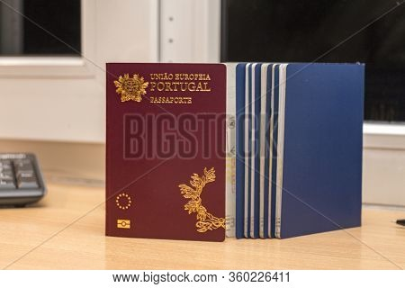 Close-up Of A Portuguese Biometric Passport Along With Other Passports During Passport Control At Th