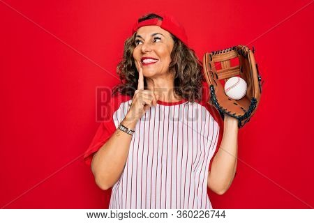 Middle age senior woman wearing baseball equiment, ball and glove over red isolated background serious face thinking about question, very confused idea