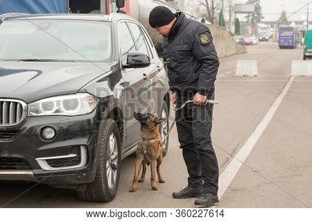 Shegini, Ukraine - November, 2018: Ukrainian Border Guard With A Service Dog Inspects Vehicles At Th