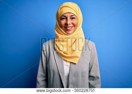 Middle age brunette business woman wearing muslim traditional hijab over blue background with a happy and cool smile on face. Lucky person.