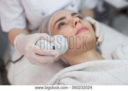 Cosmetology. Beautiful Woman Receiving Facial Skin Ultrasound Cavitation. Closeup Of Female Face Rec