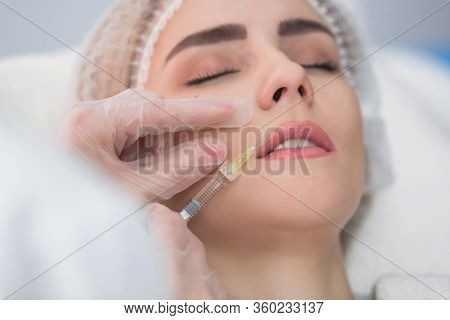 Hands Of Cosmetologist Making Injection In Face, Lips. Young Woman Gets Beauty Facial Injections In