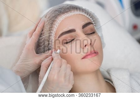 Plastic Surgery Concept. Hands In Gloves Marking Women Face.