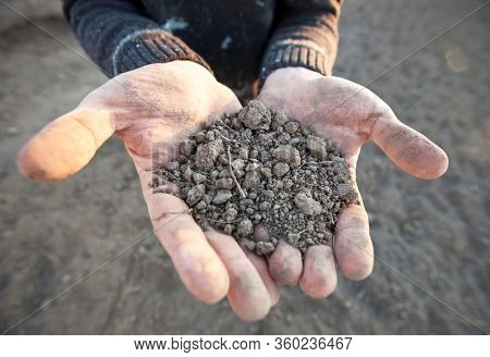 The man is holding the very dry soil in his palm. Concept of soil erosion due to lack of precipitation due to global warming