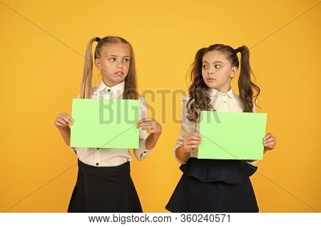 Thinking Over A Home Work. Little Children Holding Empty Sheets For Examination Work On Yellow Backg