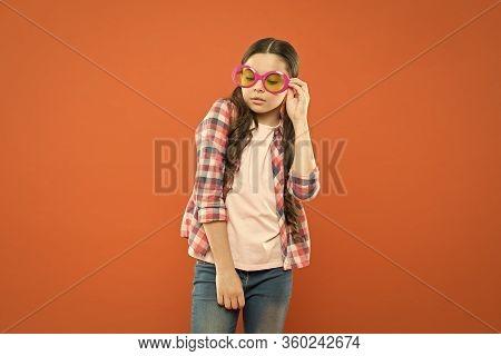Fashionable Cutie. Being Smart. Little Smart Schoolgirl On Orange Background. Child Smart Look Throu