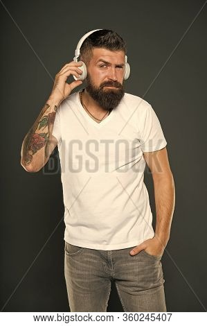 Fine Tunes. Hipster Listen To Music In Stereo Headphones. Bearded Man Wear Headphones Grey Backgroun