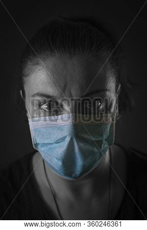 Pan(dem)ic. Close-up Of A Caucasian Woman Wearing Protective Mask. Low Key Portrait. Duotone.
