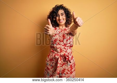 Young beautiful curly arab woman on vacation wearing summer floral dress and sunglasses approving doing positive gesture with hand, thumbs up smiling and happy for success. Winner gesture.