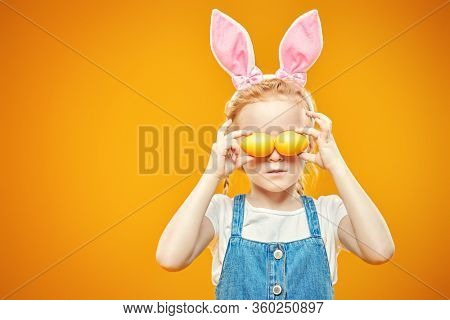 Funny little girl is posing in light t-shirt and sundress is holding Easter painted eggs on a yellow background in the Studio. Happy childhood. Easter holiday.